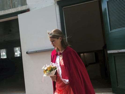 Clare Becker — The Evening Sun 2014 Apple Blossom Queen Kayla Silko makes a final walk from her dressing room to the stage area before contestants compete for her crown during the Apple Blossom Festival on Sunday.