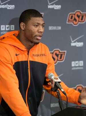 This photo provided by Oklahoma State University Athletics shows Oklahoma State basketball player Marcus Smart, left, addressing the media at a news conference in Stillwater, Okla., Sunday, Feb. 9, 2014, in regard to an altercation during an NCAA college basketball game the day before. Smart was suspended three games by the Big 12 for shoving a fan.