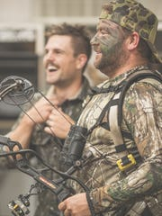 Austin Casselman, one of the founders of Catchin' Deers and CEO of Nashville-based Implement Now product branding company, smiles in full camo at Kentucky hunt camp. Behind him, Bud Fisher grins.