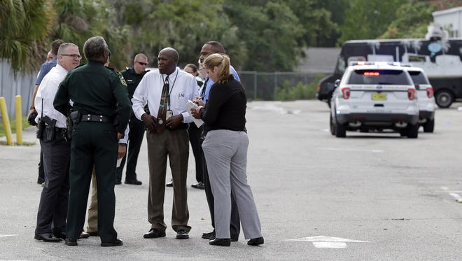 Authorities confer near the scene of a shooting in an industrial area near Orlando on June 5, 2017. The Orange County Sheriff's Office said on its official Twitter account that the situation has been contained.