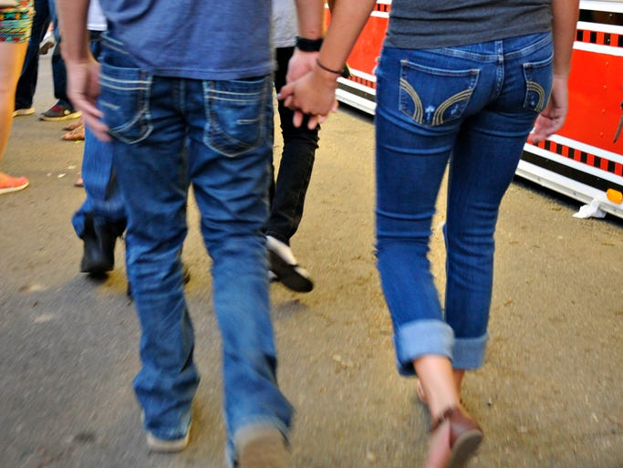 A couple holds hands as they walk around the midway at the Benton County Fair.