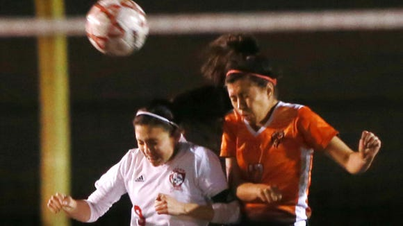 Jefferson's Abril Gomez, left, and El Paso's Priscilla Leiva leaped to head the ball.