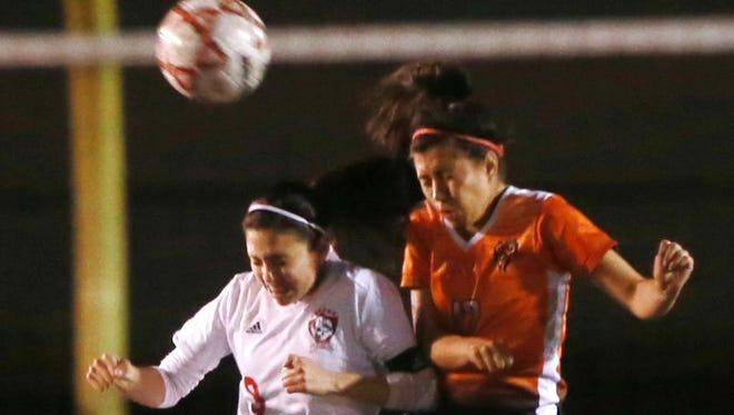 Jefferson's Abril Gomez, left, and El Paso's Priscilla Leiva leaped to head the ball.