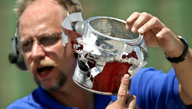 Donald Sachtleben holds up a coffee can that was destroyed by a blasting cap and two grams of explosives during an Introduction to Explosives and Weapons of Mass Destruction training session and demonstration held by the Indianapolis FBI  on July 31, 2007.