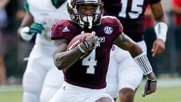 Mississippi State wide receiver Jameon Lewis (4) runs up field following a short pass reception from quarterback Dak Prescott (15) in the first half of an NCAA college football game against UAB at Davis Wade Stadium in Starkville, Miss., Saturday, Sept. 6, 2014. Mississippi State won 47-34. (AP Photo/Rogelio V. Solis)
