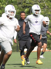 Ray Rice working with football players during a spring