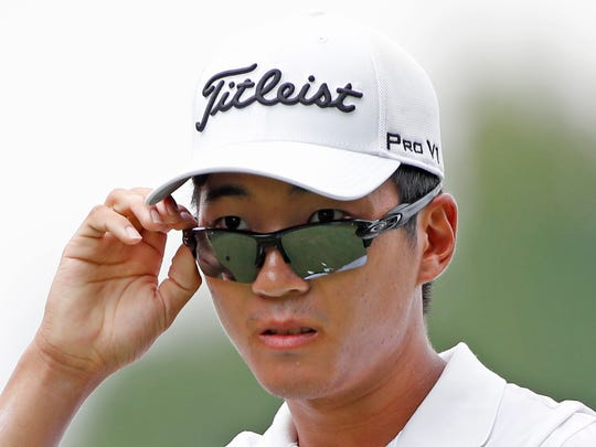 PGA golfer Michael Kim peers over his sunglasses to see where his tee shot landed on the 7th hole during the third round of the John Deere Classic golf tournament at TPC Deere Run.