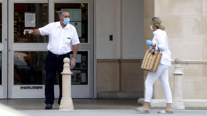 An employee of Publix wears a protective mask as he directs a shopper to join a line along the north side of the store's entrance.
