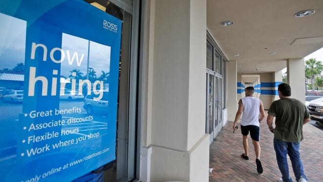 Shoppers walk past a now hiring sign at a Ross store in North Miami Beach, Fla.