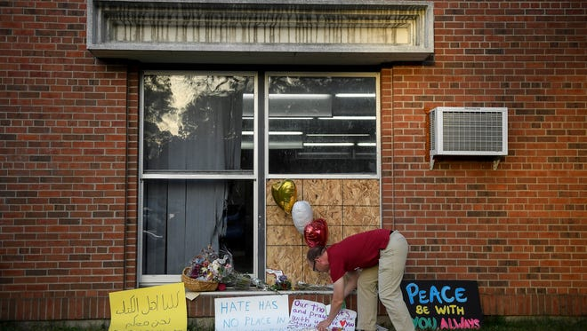 Ben Sunderlin places a sign of support near the window that was damaged during Saturday morning's attack at the Dar Al-Farooq Islamic Center in Bloomington, Minn., Tuesday, Aug. 8, 2017. More than a thousand people attended Tuesday's rally in a community-wide show of support for the Minnesota mosque following the weekend attack.
