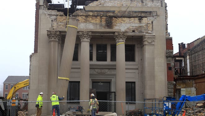 Miron Construction Co. employees remove the stone pillars from a historic bank building on Main Street in Menasha. December 23, 2014, in Menasha, Wis. .