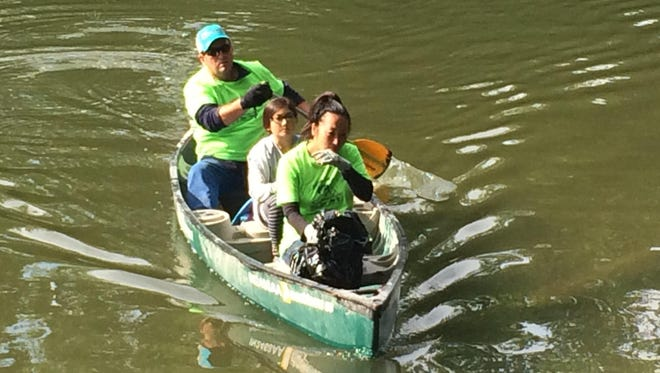 Kate Lustig and her daughter, Kaiya, rode in a canoe across the White River in Carmel after picking up trash on Saturday. It's the second year Kaiya, 9, has taken part.