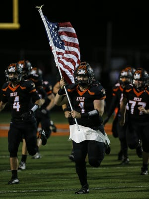 Jackson High carries a flag as Ryle takes the field prior to their 6A playoff game with Cooper.