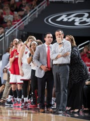 Louisville assistant coach Sam Purcell, left, and head coach Jeff Walz look on during a game.