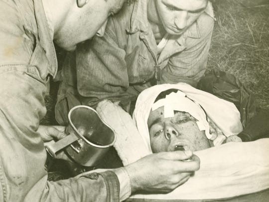 Pvt. Jimmie Wilson of Jacksonville, Fla., is given hot coffee upon reaching the Duxbury base camp following his rescue off Camels Hump after the crash of B-24 Liberatoron Oct. 16, 1944 He lost both hand and both feet due to amputation.