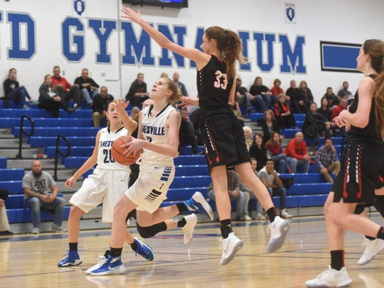 Zanesville's Madison Winland goes up for a shot against New Philadelphia's Anne-Marie Monaco in Wednesday's ECOL contest at Winland Memorial Gymnasium.