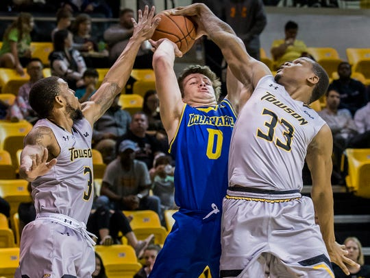 Delaware's Ryan Daly (No. 0) has his shot blocked by Towson's Eddie Keith II (No. 33) as Deshaun Morman (No. 3) also defends in the first half of the University of Delaware's 83-56 loss to Towson University at the SECU Arena in Towson, Md. on Thursday night.