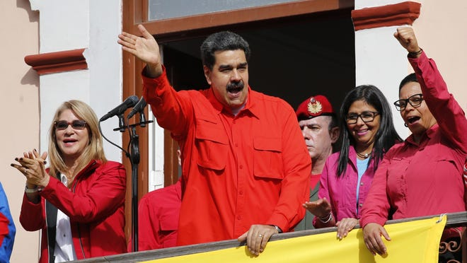 Venezuela's President Nicolas Maduro, center, and first lady Cilia Flores, left, interact with supporters from a balcony at Miraflores presidential palace during a rally in Caracas, Venezuela, Jan. 23, 2019. At a competing rally, opposition leader Juan Guaido declared himself interim president until new elections can be held, to which Maduro responded by cutting off diplomatic relations with the United States and said American diplomats had 72 hours to leave the country.