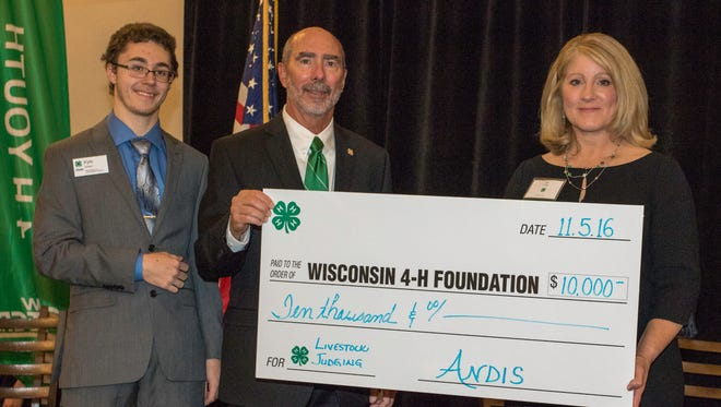 4-H Leadership Council Member Kyle Girard, and Dale Leidheiser and Jill Nieskes of the Wisconsin 4-H Foundation accept Andis Foundation's donation.
