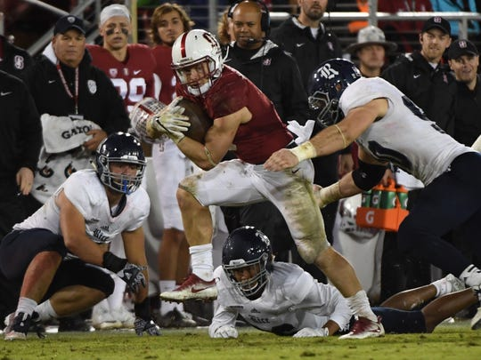 FILE -- Stanford Cardinal running back Christian McCaffrey (5) runs against Rice Owls cornerback Brandon Douglas (26), defensive end Brady Wright (40), and defensive end Blain Padgett (90) during the second quarter at Stanford Stadium.