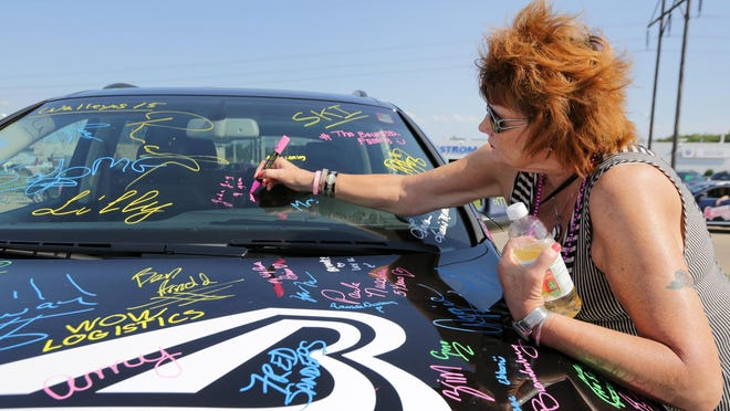 Shirley Wunderlich signs a car Saturday in honor of her daughter, Joda Joy, a nine-year cancer survivor, as part of Bergstrom Automotive's annual Drive for a Cure fundraiser to support breast cancer research.