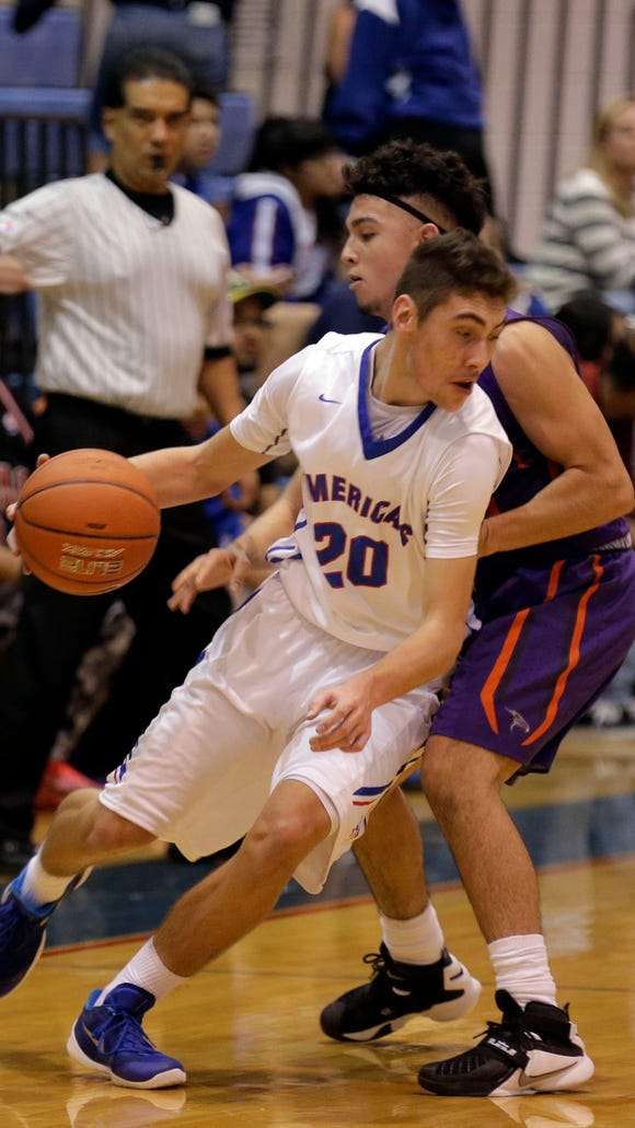 Americas guard Sebastian Andrade dribbles around the defensive pressure being applied at half court by Falcons guard Joel Martinez at Americas gym Tuesday night. The Trail Blazers led throughout the night and pulled away in the second half to win 79-44.