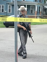 A state trooper armed with a semiautomatic rifle patrols