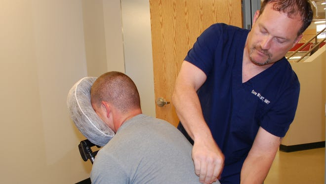 Licensed Massage Therapist Gene Watson performs a chair massage  at the Malmstrom Fitness Center July 13.