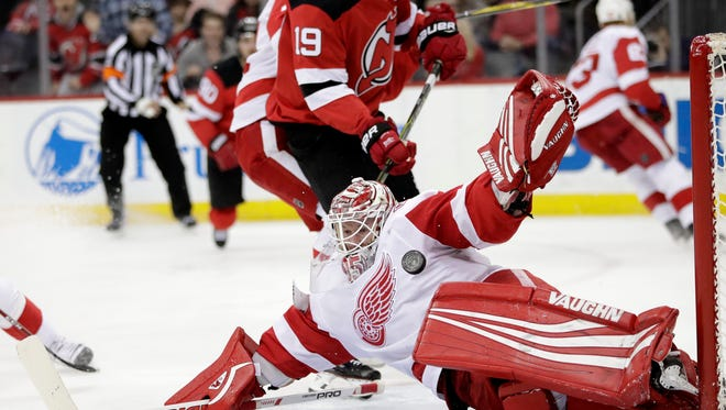 Detroit Red Wings goalie Jimmy Howard, right, blocks a shot by New Jersey Devils center Travis Zajac (19) during the second period of an NHL hockey game Wednesday, Dec. 27, 2017, in Newark, N.J. (AP Photo/Julio Cortez)