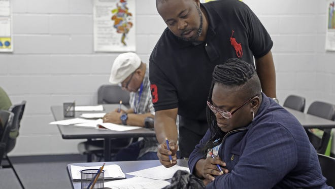 GED teacher Charles Williams helps Naesha Huggins with math work at the ACE center for Adult and Community Education. Huggins, 37, says the quiet and respectful environment at ACE has given her the confidence she needed to pursue her GED over two decades after dropping out of high school.
