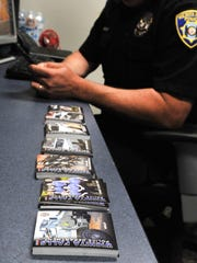 Wichita Falls police officer Timothy Johnson displays the departments newest outreach method, trading cards. Johnson said the cards will have each officer's picture, biography and will made available to each officer to be given out.