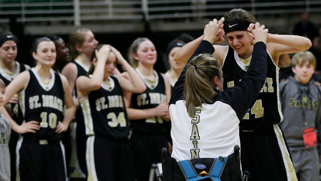 St. Ignace's Dorene Ingalls gets high fives from Margo Brown as they wait to get their championship trophy after their 64-60 overtime win over Pittsford in the MHSAA Class D girls basketball final on Saturday, March 21, 2015 in East Lansing.