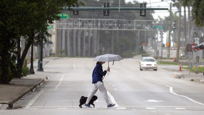A woman crosses Okeechobee Boulevard in downtown West Palm Beach as the rain starts Sunday morning, May 24, 2020.