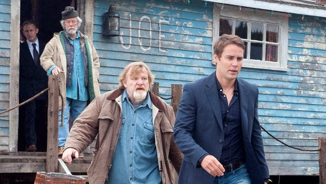 """Brendan Gleeson, center, and his small-town neighbors try to lure a doctor (Taylor Kitsch) to move there, in a scene from """"The Grand Seduction."""""""