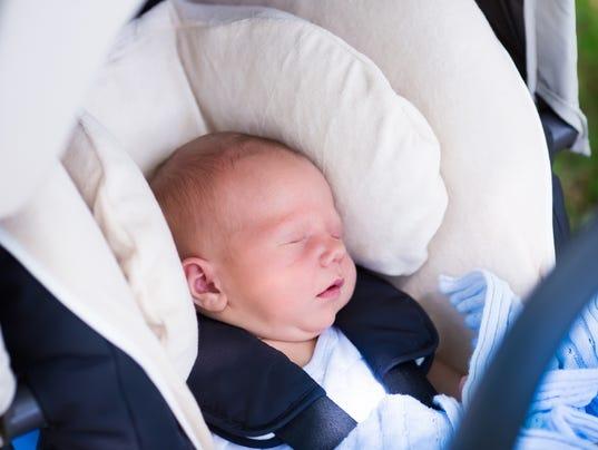Newborn baby boy sleeping in car seat