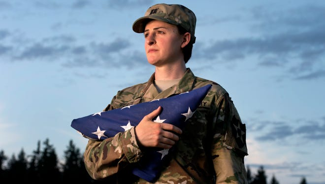 "In this Aug. 28, 2015 file photo, Capt. Jennifer Peace holds a flag as she stands for a photo near her home in Spanaway, Wash. Peace has been been deployed around the world, including Iraq and Afghanistan. When an officer suggested she leave the military rather than deal with the fallout of being a transgender soldier, Peace was taken aback. ""I couldn't believe he said that. I've been in the military for 11 years. It's everything to me. It's what I do. It's as much a part of me as anything else."""