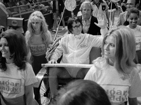 Bobby Riggs rides in a carriage pulled by women in