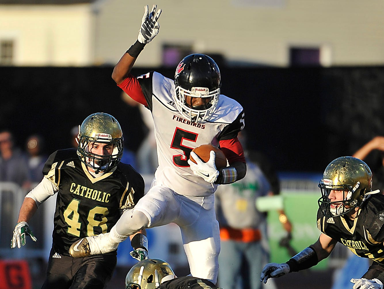 Pearl-Cohn's Rontavious Groves (5) hurdles over a Knoxville Catholic defender during the Class 4A BlueCross Bowl Saturday.