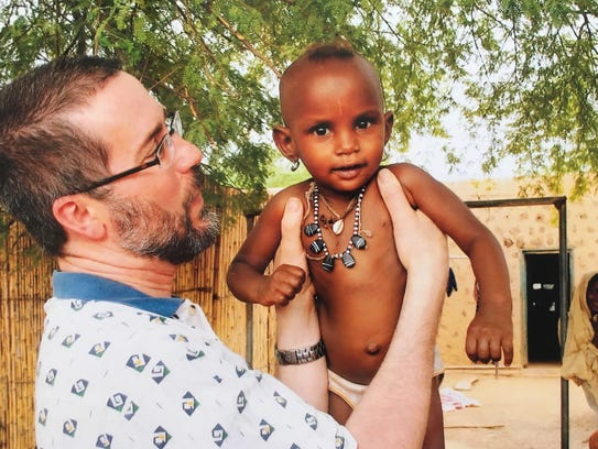 Dr. Jim Hines holds a child while working as a missionary