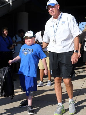 MTSU head football coach Rick Stockstill walks Colton Sheets, 9, onto the field during practice Thursday, Sept. 17, 2015. Colton Sheets, who currently in remission from leukemia, will be MTSU's football honorary captain for the Saturday game against Charlotte.