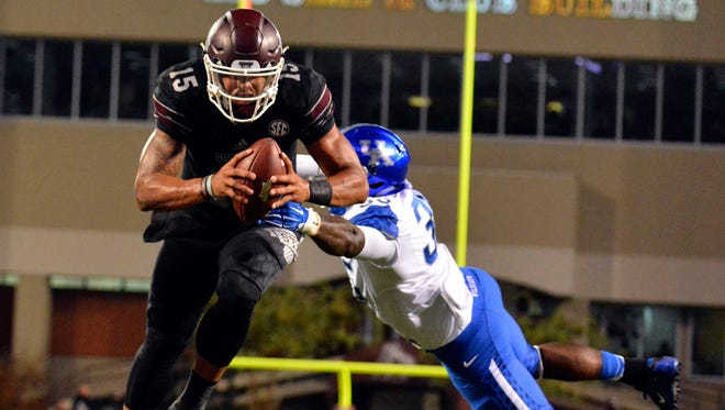 Mississippi State Bulldogs quarterback Dak Prescott (15) scores a touchdown after breaking a tackle by Kentucky Wildcats defensive end Denzil Ware (35) during the first quarter of the game at Davis Wade Stadium.