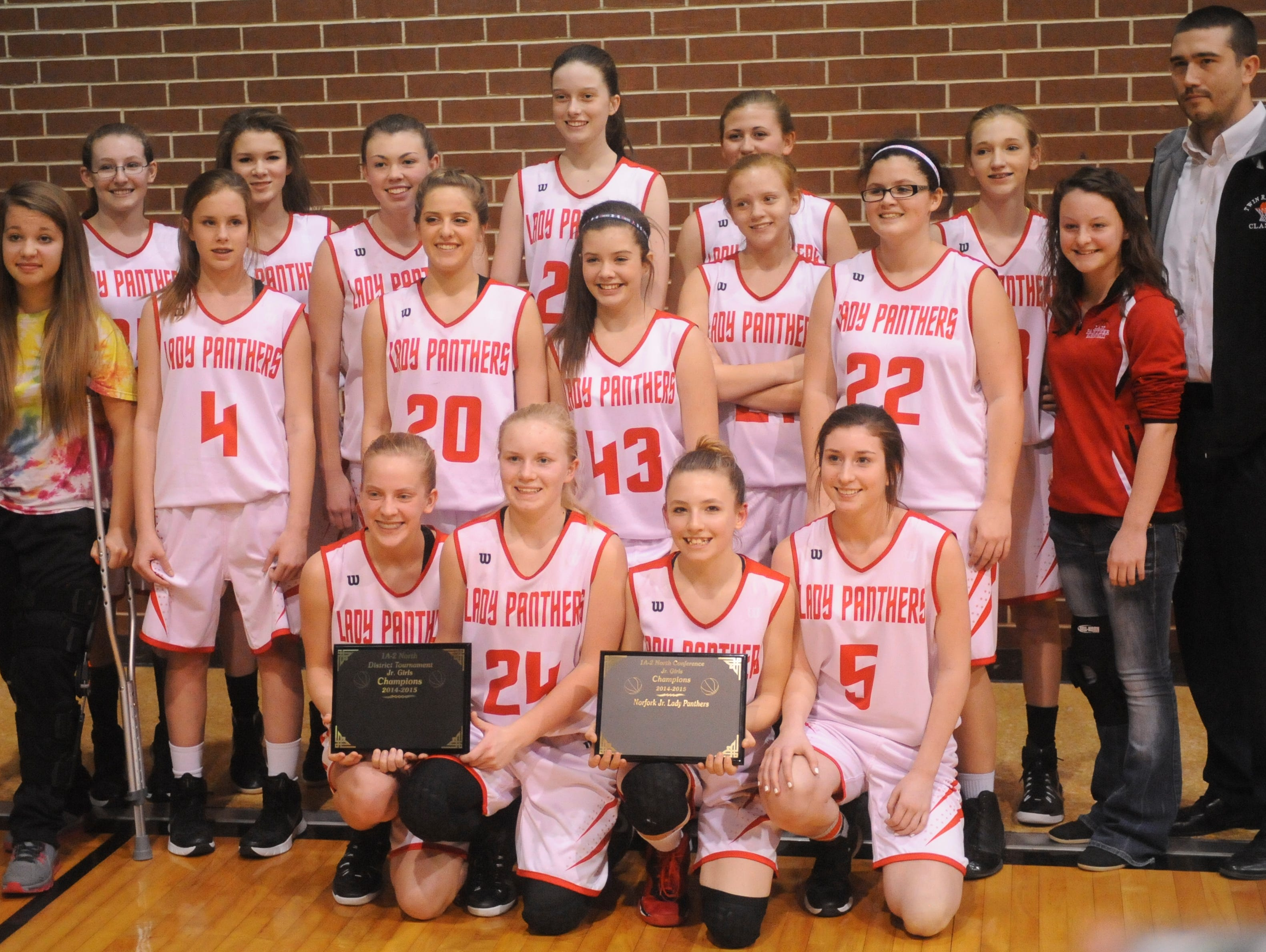Members of the Norfork Junior Lady Panthers celebrate their 1A-2 North Junior District championship by posing for a team photo after their 40-22 victory over Izard County on Saturday night at Viola.