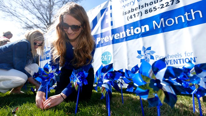 Holly Beadle, executive director at Isabel's House Crisis Nursery, plants pinwheels with Isabel's house and Cox Health employees on Friday, April 1, 2016. Pinwheels were planted for every child Isabel's House served last year, a total of 387.