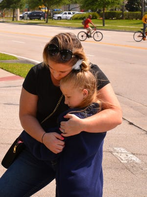 Dawn Laing hugs her daughter Brittley at the site of the accident, they brought ballons and flowers. Every few minutes a car would stop and a parent with children, friend or acquaintance would add something to the roadside memorial for the young boy killed on his bike riding home from school Wednesday on Eldron Blvd. in Bayside Lakes.
