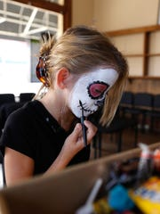 Tayli Esquibel works on her makeup, Monday during Boopalooza on Main Street in Farmington.