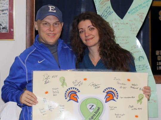 Zack Brown and his wife, Ginger, hold up a signed card from members of the Thomas A. Edison football team at their home in Pine City. In the background is a signed ribbon from Watkins Glen High School.