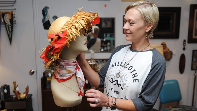 Sarah Kerns, owner of Squidbait and Maggie's Curiosity Shop, adjusts jewelry on a mannequin Wednesday at her store on Walnut Street in downtown Chillicothe.