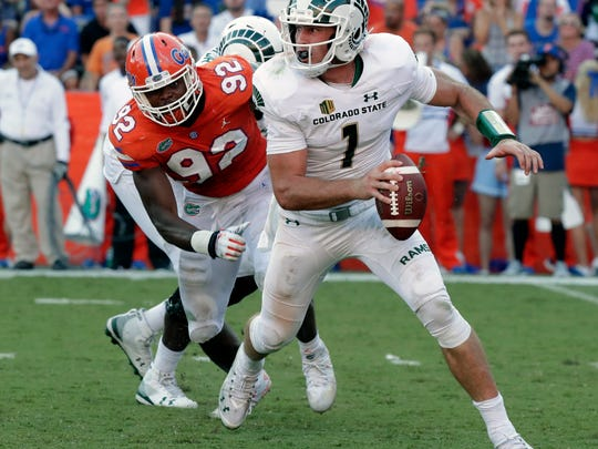 Colorado State quarterback K.J. Carta-Samuels (1) scrambles as he is chased by Florida defensive lineman Jabari Zuniga (92) during the second half of an NCAA college football game, Saturday, Sept. 15, 2018, in Gainesville, Fla. (AP Photo/John Raoux)