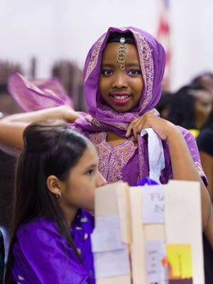 Natalie Opher, age 10, adjusts her Indian sari at a summer program with an around-the-world exhibit at Serviam Girls Academy in New Castle on Thursday.