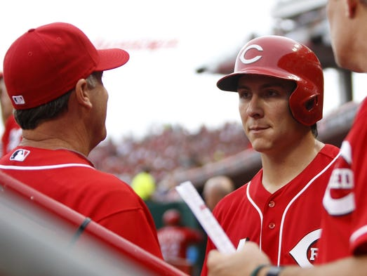 Homer Bailey (right) talks to manager Bryan Price (left) during the second inning against the Philadelphia Phillies at Great American Ball Park.